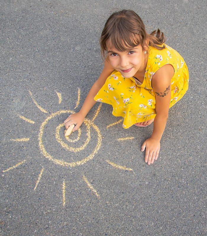 The child draws the sun on the asphalt. Selective focus. nature.